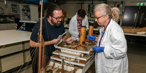 Conservation treatment of the SS ORONTES model ship (00055182), 2019. Conservators (from left), Jeff Fox, Nick Flood, and Agata Rostek-Robak at work in the Cons Lab.