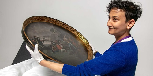Unpacking objects for the Bligh exhibition. Registrar Anupa Shah carefully handles one of the new acquisitions, the object 00055335 (tea tray featuring death of Captain Cook).