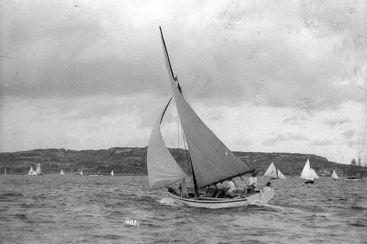 A couta type yacht sailing north on Sydney Harbour with South Head and Watson's Bay in distance. ANMM Collection 00011020. William James Hall.