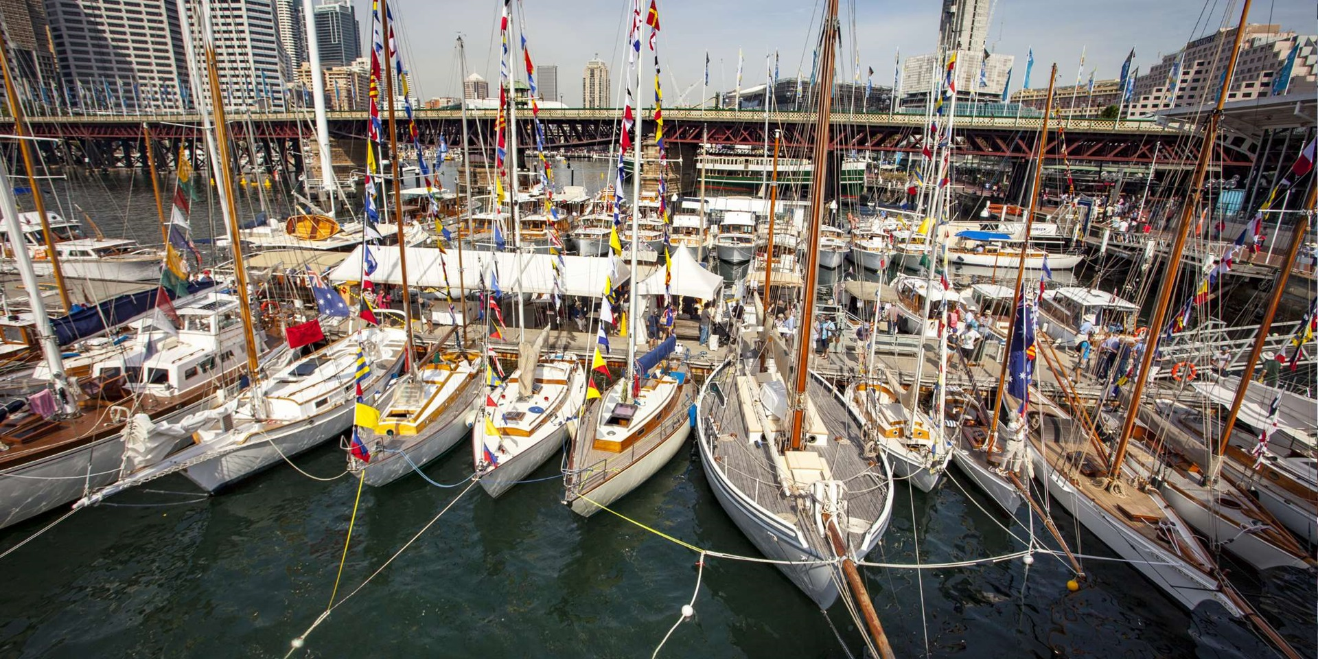 Classic Wooden Boat Festival 2016. Masted wooden boats pictured moored together with the Pyrmont Bridge in the background.
