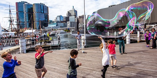 A group of children playing with giant bubbles on the museum's performance platform