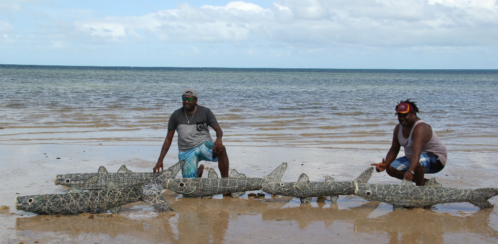 Artists Jimmy J Thaiday and Jimmy K with their ghost net mullet. Photography by Lynnette Griffiths.