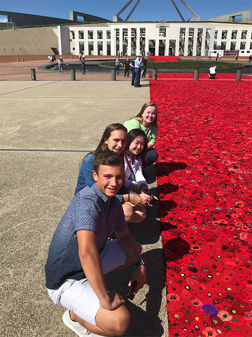 Parliament House Canberra with students beside the poppy carpet.