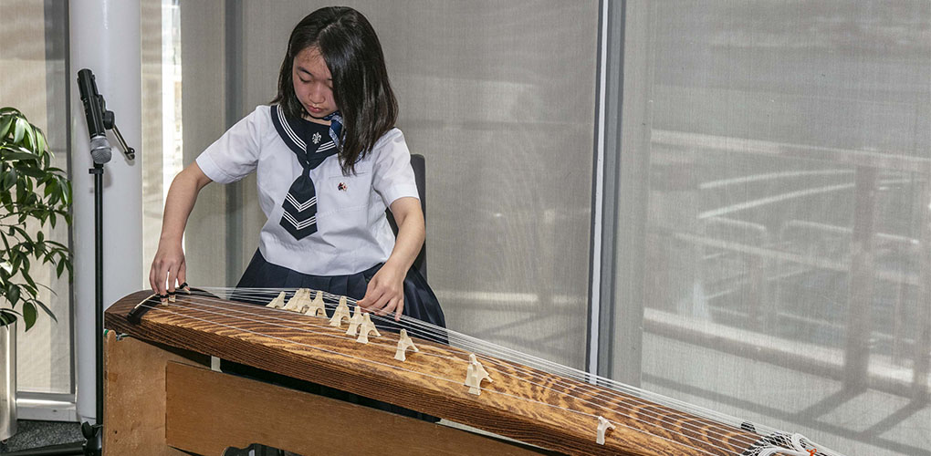 Japanese youth ambassador, Saya, plays a song of peace on a traditional instrument, the koto.